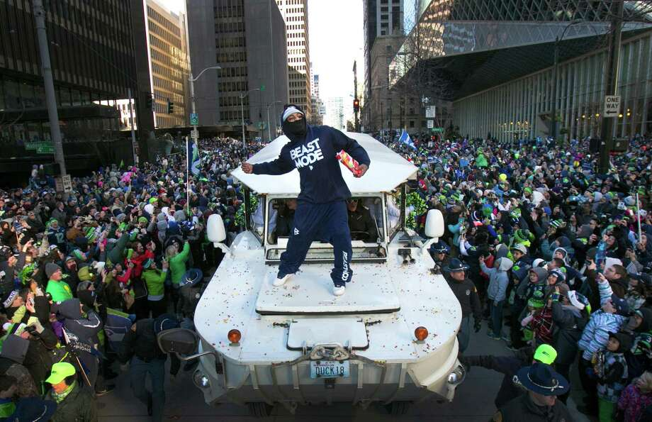 Marshawn Lynch throws Skittles back to the 12th Man during the Super Bowl Championship Parade on Wednesday, February 5, 2014 in downtown Seattle. An estimated 700,000 people came out to celebrate with Seattle's championship team. Photo: JOSHUA TRUJILLO, SEATTLEPI.COM / SEATTLEPI.COM