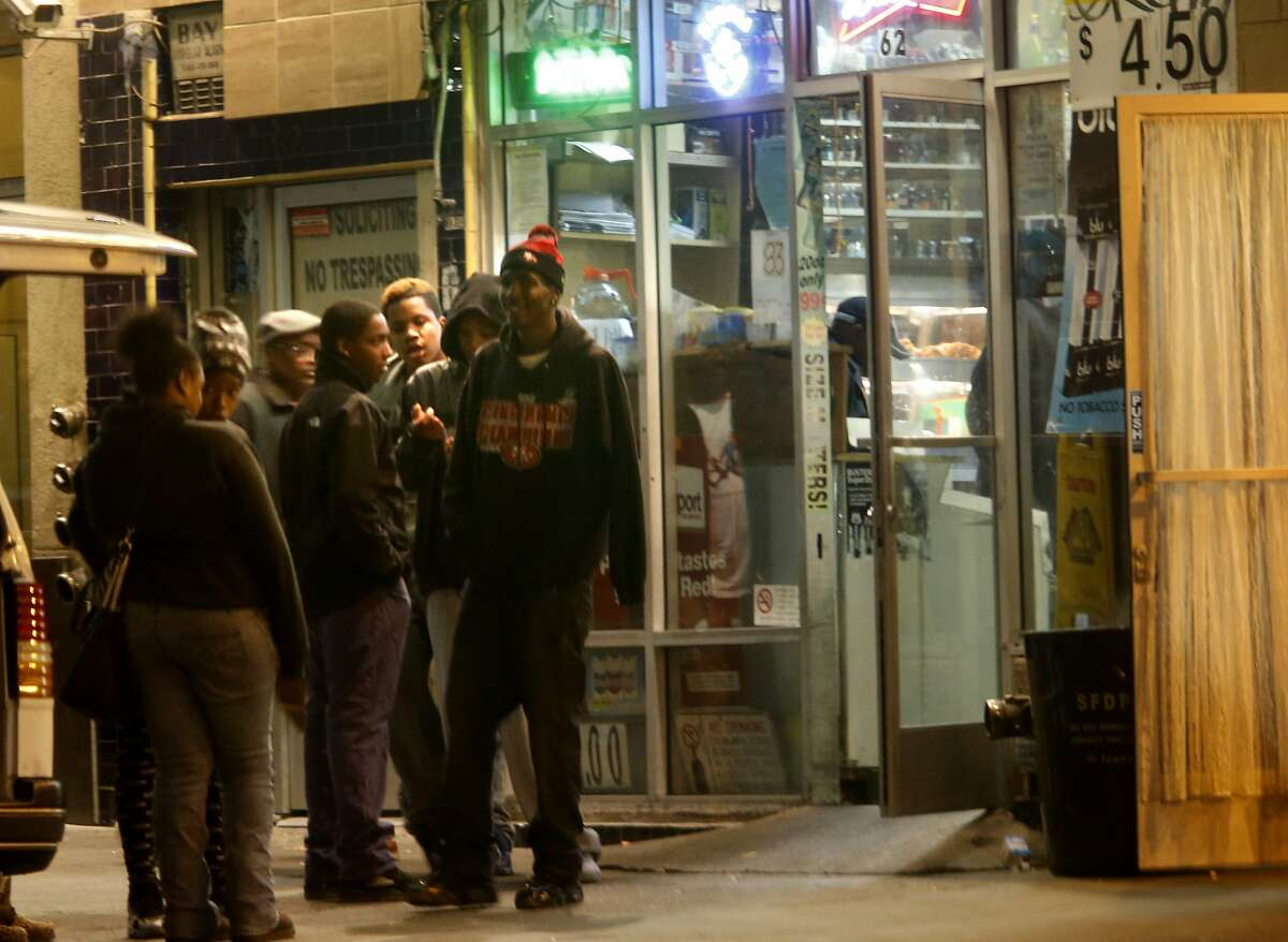A group of young people congregate outside a liquor store on Turk Street Tuesday February 4, 2014. Community and homeless organizers have gotten