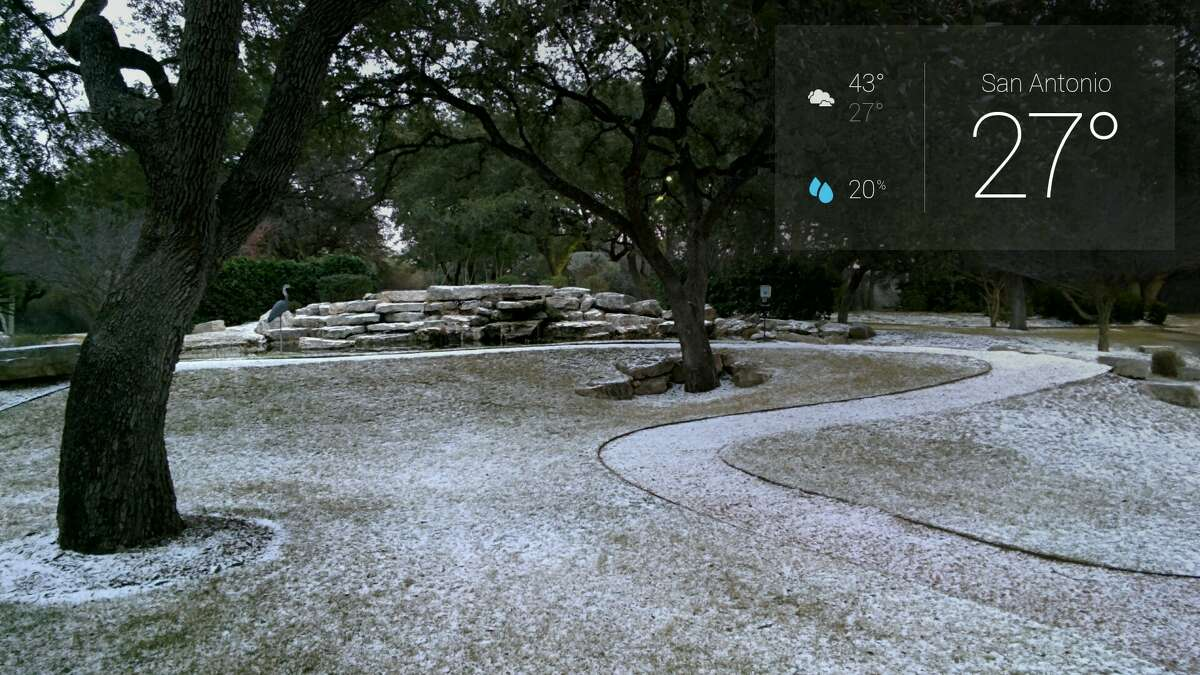 A reader uses Google Glass to take photos of graupel, which is snow encased in ice, on Thursday morning, Feb. 6, 2014.