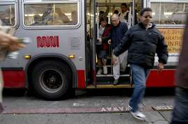 MUNI riders transfer at the bus stop on the corner of Fillmore and Geary Streets in the San Francisco, Calif on Thursday January 28, 2010. With the Municipal Transportation Agency facing a $53 million budget deficit next year, they are considering fare increases to some of the most vulnerable riders who use the system. The the problem could balloon to almost $103 million if proposed fare increases and service cuts -- which would be among the deepest in Muni's history -- aren't approved quickly to balance this year's budget shortfall. Among the recommendations: reduce the frequency of bus and rail service on most routes, equivalent to a 10 percent cut systemwide; charge Fast Pass users a premium for using express buses or cable cars; double the cost of discounted monthly passes for seniors, youth and the disabled to $30.
