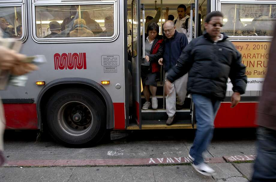 MUNI riders transfer at the bus stop off Geary Street. Photo: Michael Macor, The Chronicle