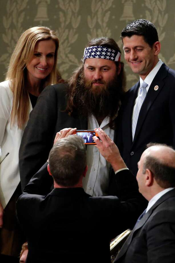 """Duck Dynasty's"" Willie Robertson, center, and his wife Korie, pose with Rep. Paul Ryan, R-Wis., before President Barack Obama's State of the Union address on Capitol Hill in Washington, Tuesday, Jan. 28, 2014. Photo: Charles Dharapak, AP / AP"