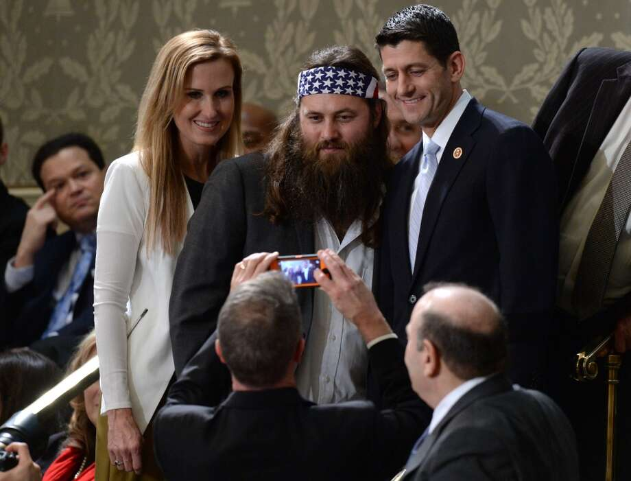 "Willie Robertson of ""Duck Dynasty"" poses for a picture with Rep. Paul Ryan, R-Wis. and his wife, Janna, before the speech."