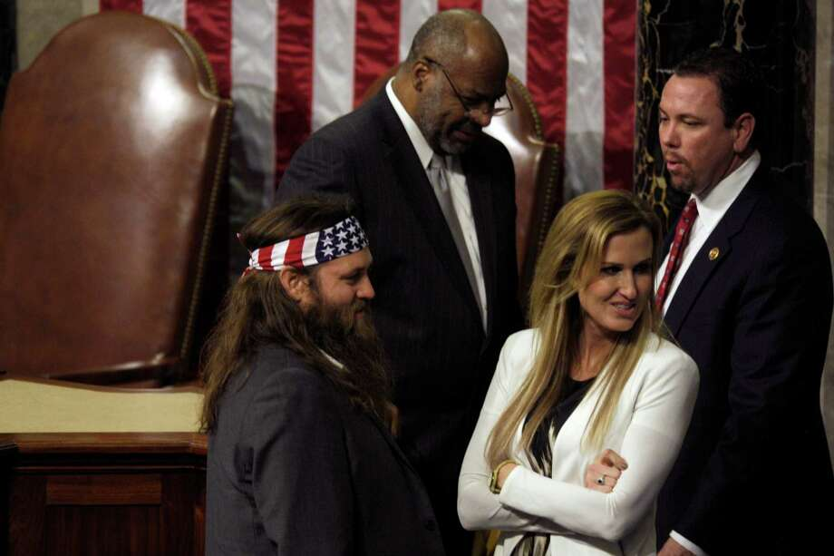 Duck Dynasty's Willie Robertson and his wife Korie walk on the floor of the House after President Barack Obama gave the State of the Union address on Capitol Hill in Washington, Tuesday Jan. 28, 2014. (AP Photo/Susan Walsh) Photo: Susan Walsh, Associated Press / AP