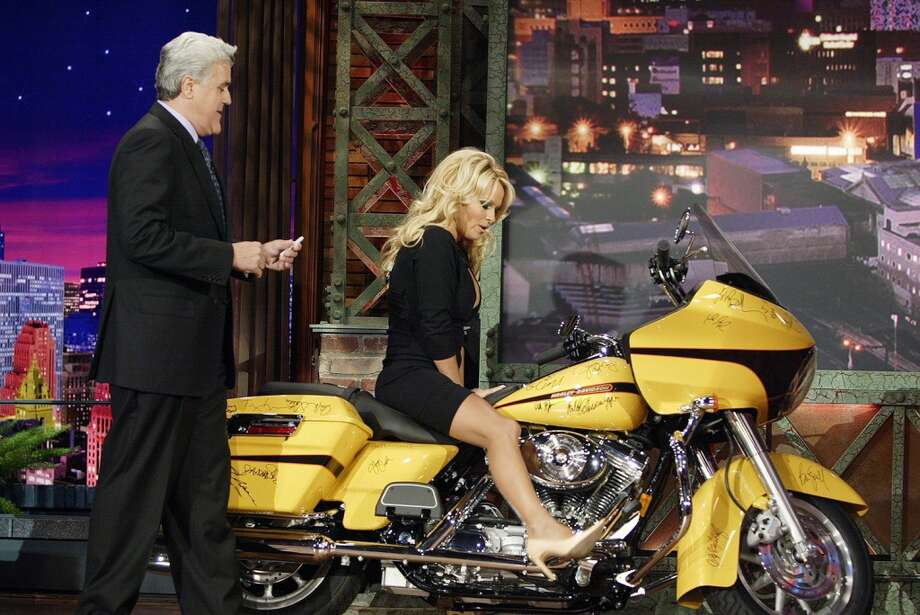Jay Leno with actress Pamela Anderson making a surprise appearance to autograph a motorcycle for charity in 2005. Photo: NBC, NBC Via Getty Images