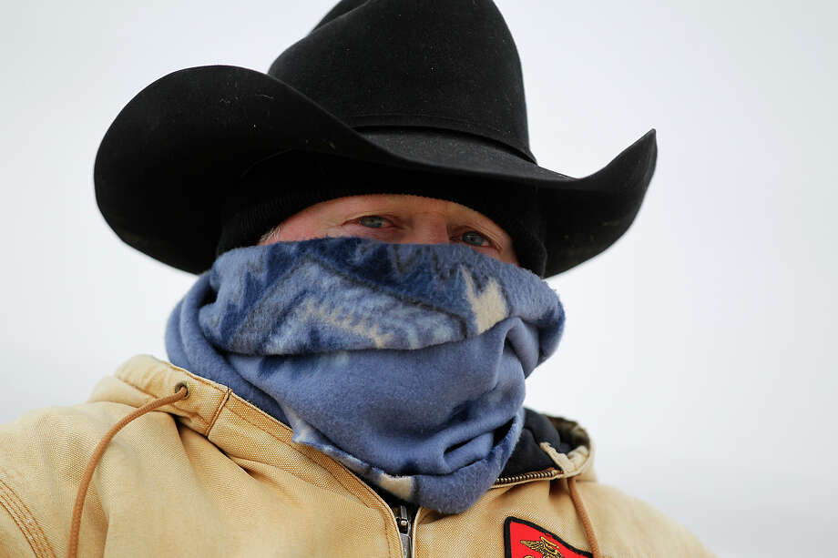Pastor C.J. Tillinghast bundles up as the Laredo Trail Ride start their day after camping at the Country Gold Dance Hall at 7504 Old Pearsall Road, Thursday, Feb. 6, 2014. They were headed to their lunch rendezvous at Moursund Road and Loop 410, but due to the cold weather, made it to the intersection of Fischer Road and IH-35 before calling it quits. Tillinghast is the pastor of the United Methodist Church of Cotulla. Photo: Jerry Lara, San Antonio Express-News / ©2013 San Antonio Express-News