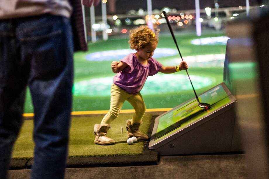 Elle Wooden, 2, attempts to get another ball from the bay at Top Golf during the Suits and Boots party Saturday January 25th in Houston. Suits and Boots is a charity event supporting Heroes Project where party goers wore bathing suits and/or boots. (Michael Starghill, Jr.) Photo: Michael Starghill Jr.
