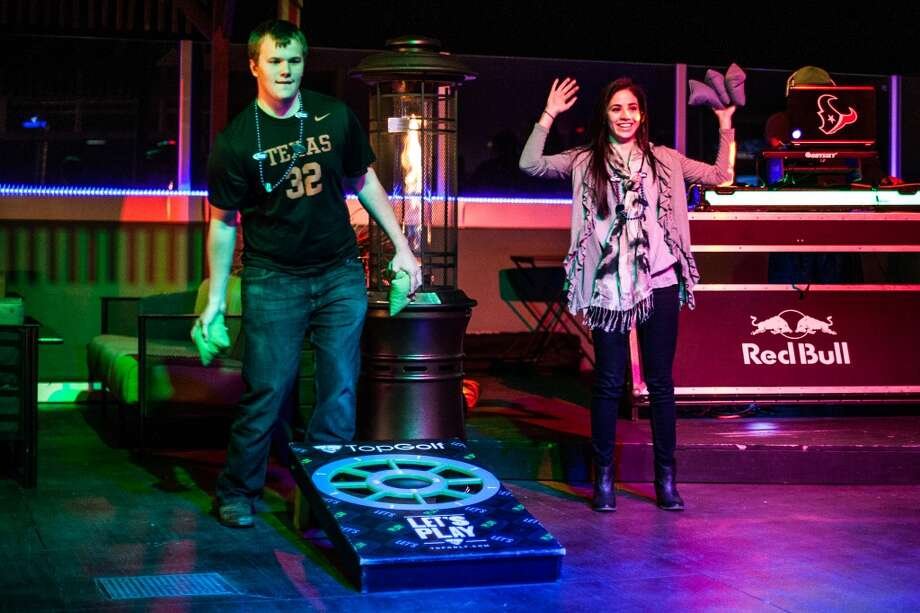 Jared Alford and Natalie Hager play a game of cornhole on the dancefloor at Top Golf during the Suits and Boots party Saturday January 25th in Houston. Suits and Boots is a charity event supporting Heroes Project where party goers wore bathing suits and/or boots. (Michael Starghill, Jr.) Photo: Michael Starghill Jr.