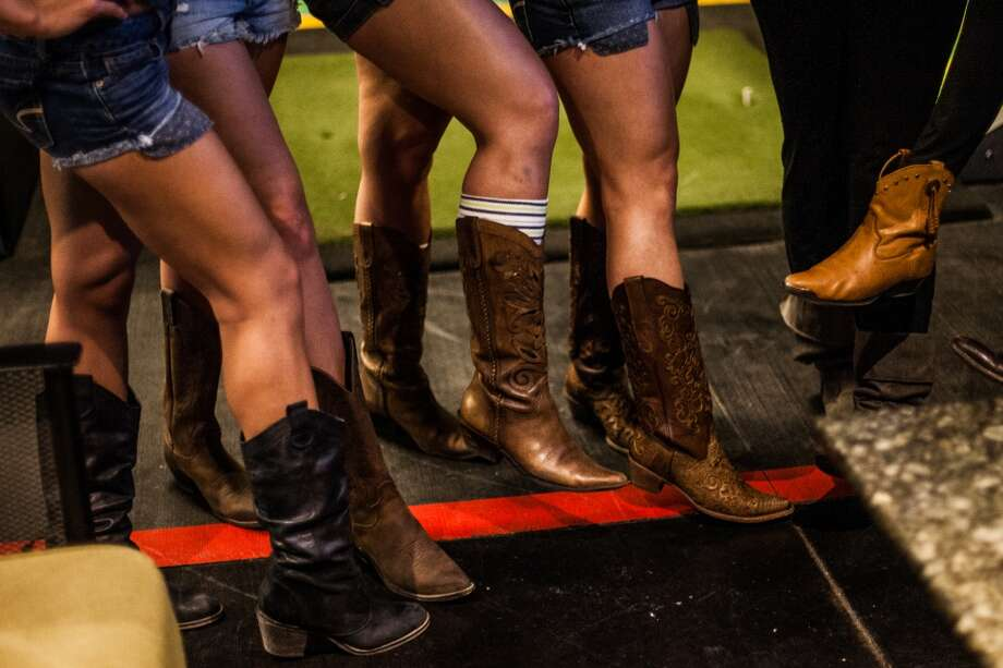 Party-goers show off their boots at Top Golf during the Suits and Boots party Saturday January 25th in Houston. Suits and Boots is a charity event supporting Heroes Project where party goers wore bathing suits and/or boots. (Michael Starghill, Jr.) Photo: Michael Starghill Jr.