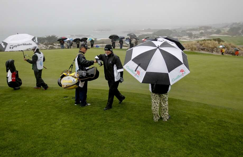 Wayne Gretzky makes birdie at the 2nd as a rain delay is called after they finished the hole, at Spyglass Hill Golf Course during round 1 at the Pebble Beach National Pro-Am golf tournament  on Thursday Feb. 6,  2014, in Pebble Beach, Calif. (Michael Macor/The Chronicle) Photo: Michael Macor, The Chronicle