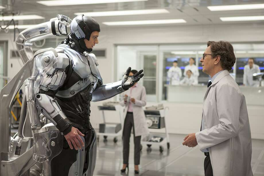 "Joel Kinnaman (left) is the human-robot cop and Gary Oldman the scientist who engineers his transformation in ""RoboCop."" Photo: Kerry Hayes, Sony Pictures"