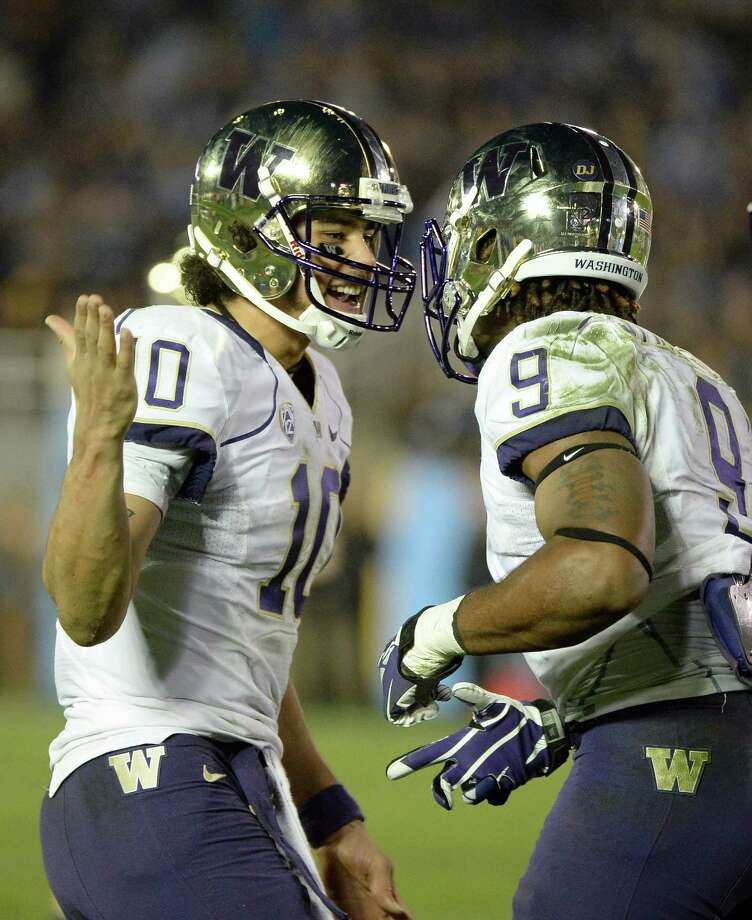Cyler Miles, left, of the Washington Huskies celebrates a Damore'ea Stringfellow touchdown during the fourth quarter against UCLA on Nov. 15, 2013, at the Rose Bowl in Pasadena, Calif. Photo: Harry How, Getty Images / 2013 Getty Images