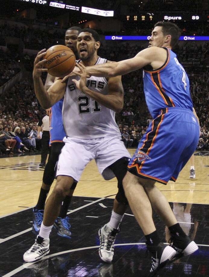 San Antonio Spurs' Tim Duncan loses the ball under pressure from Okahoma City Thunder's Kevin Durant, left, and Nick Collison during the second half at the AT&T Center, Wednesday, Jan. 22, 2014. The Thunder won 111-105. Photo: Jerry Lara, San Antonio Express-News