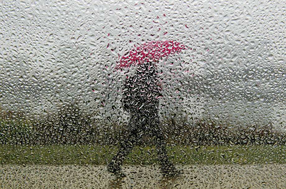 A pedestrian walks along Lake Merritt in Oakland, Calif., on Thursday, February 6, 2014, under an umbrella as a storm pushed through the area. The Bay Area received some much-needed rain on Thursday. Photo: Carlos Avila Gonzalez, The Chronicle