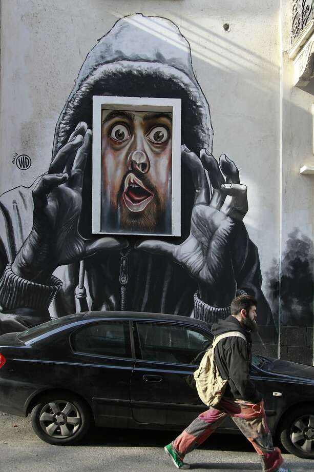 Beware of Greeks in windows:A bug-eyed man seems to be pressing his face against a window pane in this graffiti 