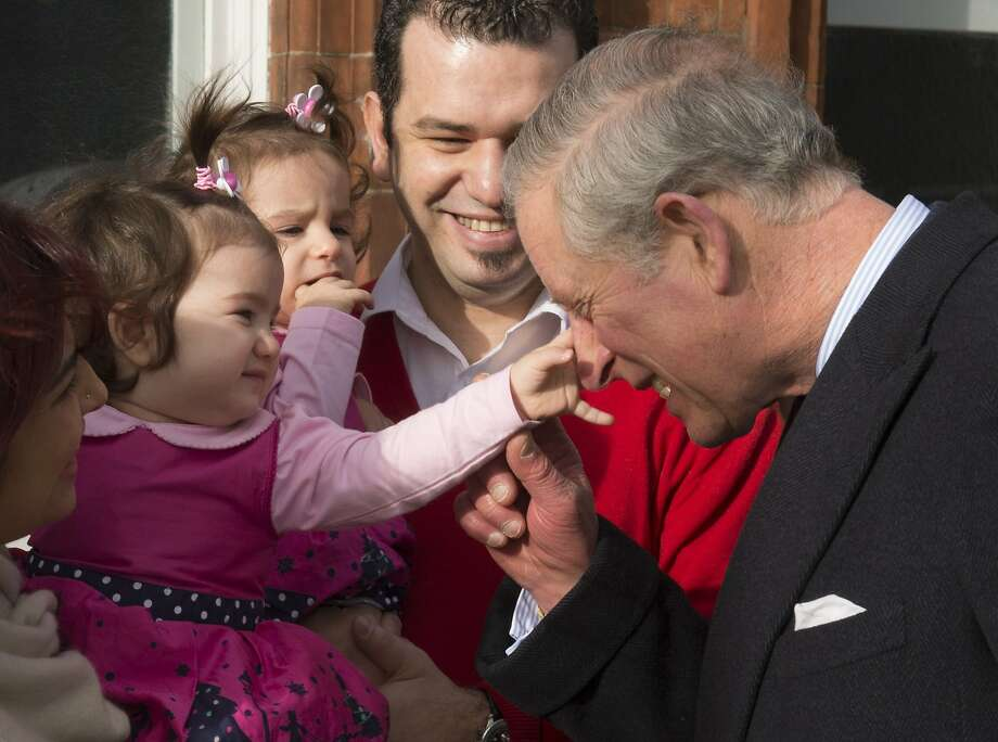 Pleased to meet Your Royal Sinus:Kayla Akbasak, about 1 year old, squeezes Charles' nose during the Prince of Wales' visit with her parents, 