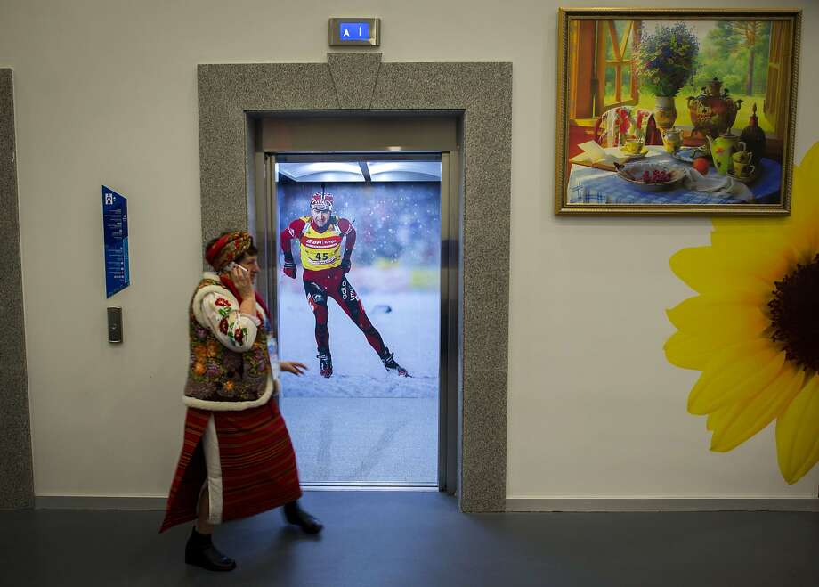 Sochi ski lift: A Russian woman in a traditional folk dress talks on a cell phone next to an elevator decorated with a poster of Norwegian biathlon champion Ole Einar Bjoerndalen at a Sochi Winter Olympics facility. Photo: Odd Andersen, AFP/Getty Images