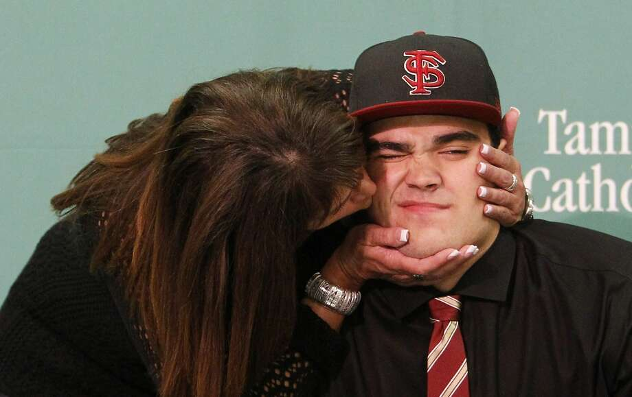 Aww, Mom, not here. Everybody's watching: Michele Martinez kisses her son, Corey, during NCAA college football National Signing Day at Tampa Catholic High School in Tampa, Fla. Corey signed with Florida State. Photo: Borchuck, James, Associated Press