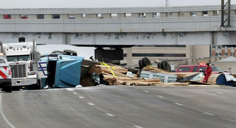 Workers position a tow rig, left, to clear an overturned truck full of lumber on the curved exit ramp from I 35 south to I 10 west just north of downtown.  Thursday Feb. 6. 30, 2014. Photo: Bob Owen, San Antonio Express-News / ©2013 San Antonio Express-News