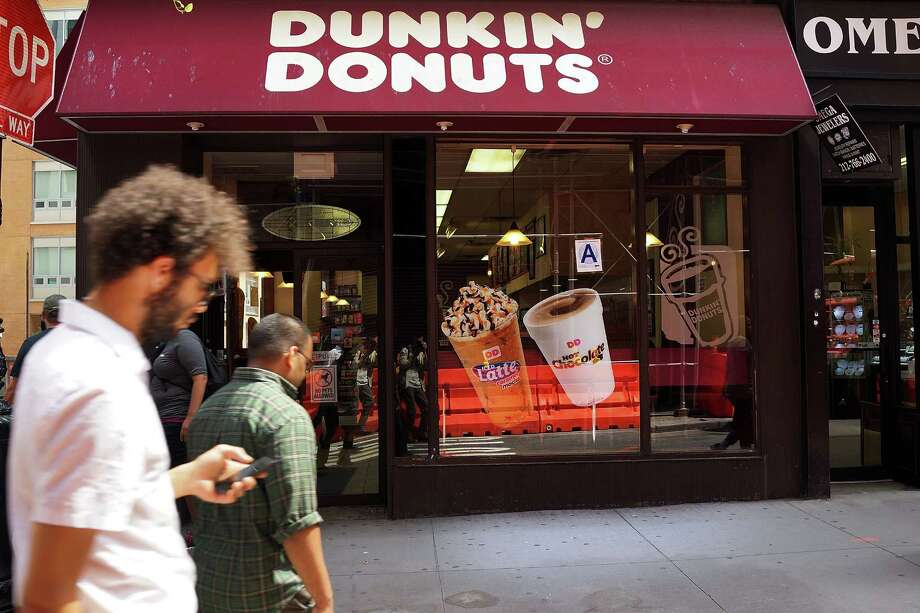 NEW YORK, NY - AUGUST 26: People walk by a Dunkin' Donuts store on August 26, 2013 in New York City. Due to minimum wage and overtime violations, the U.S. Labor Department announced that the operator of 55 Dunkin' Donuts franchises in both New Jersey and on New York's Staten Island will  have to pay 64 employees nearly $200,000 in back wages. (Photo by Spencer Platt/Getty Images) ORG XMIT: 178510286 Photo: Spencer Platt / 2013 Getty Images