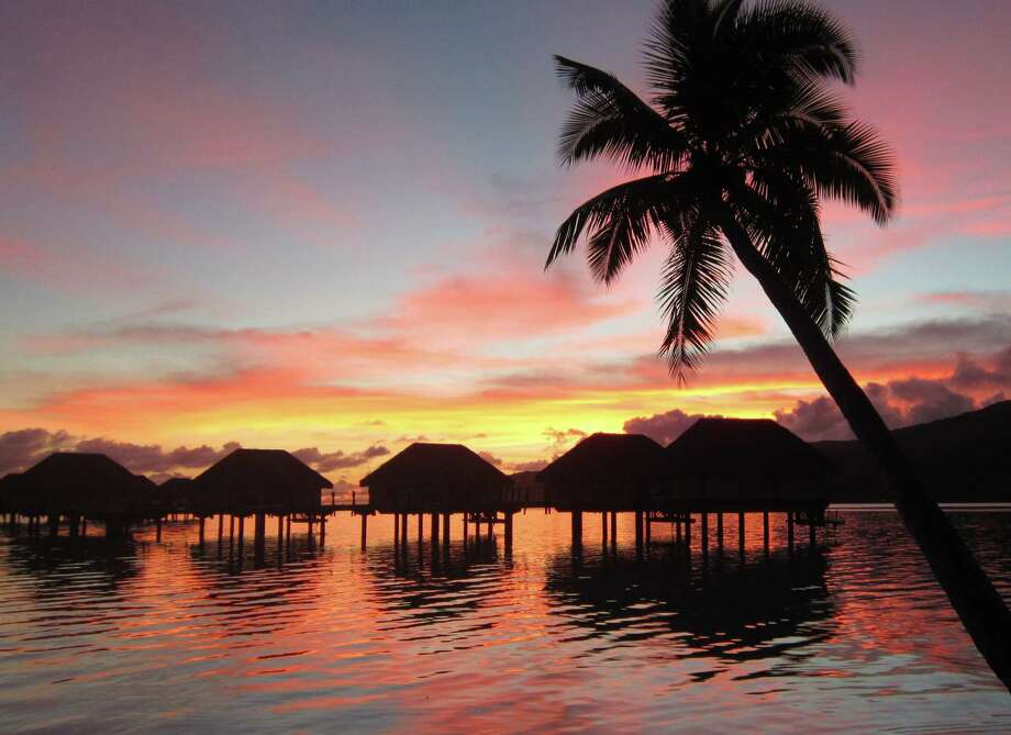 French Polynesia's sensational sunsets come up to the doorsteps of over-the-water bungalows jutting out into a sparkling lagoon. For daytime eye candy, bungalows have glass floor panels for viewing the South Pacific's colorful sea life. Photo: Michelle Newman / For The Express-News
