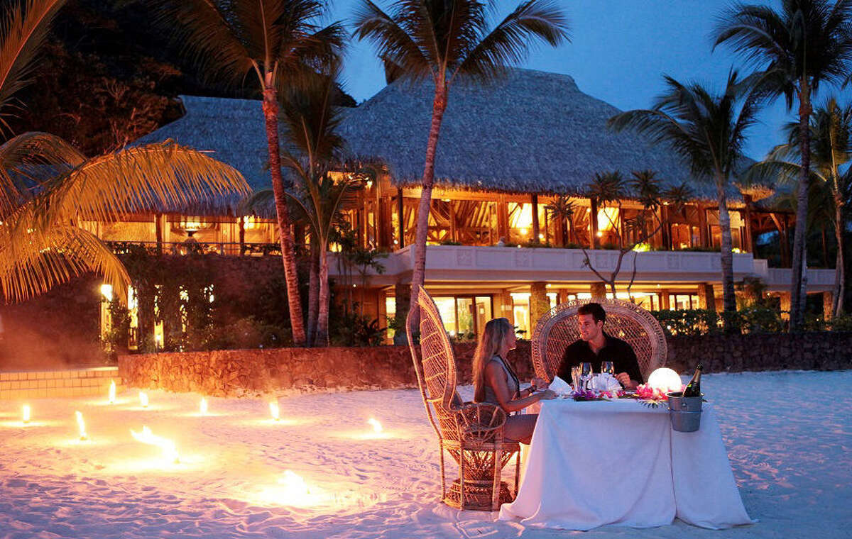 A romantic dinner for two on the beach sets the scene for romance at the Hilton Bora Bora Nui in French Polynesia.