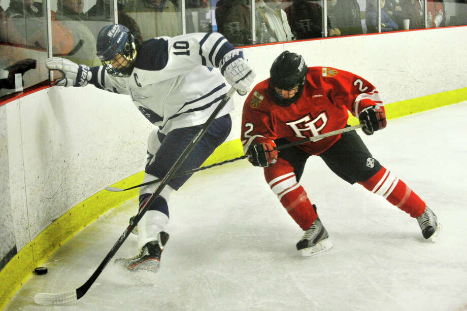 Darien's Jack Massie shields the puck from Fairfield Prep's William Burke Smith during their hockey game at Darien Ice Rink in Darien, Conn., on Feb. 6, 2014. Darien won in overtime, 3-2. Photo: Jason Rearick / Stamford Advocate