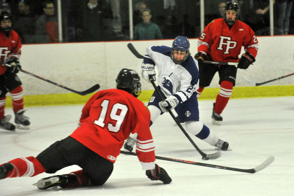 Darien's Jack Pardue shoots and scores while under pressure from Fairfield Prep's Steven Bayles during their hockey game at Darien Ice Rink in Darien, Conn., on Feb. 6, 2014. Darien won in overtime, 3-2.