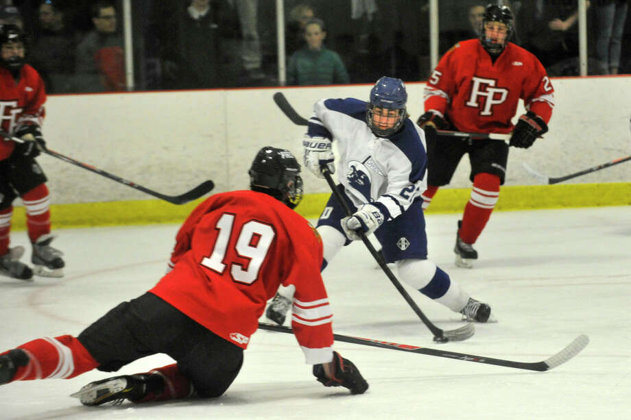 Darien's Jack Pardue shoots and scores while under pressure from Fairfield Prep's Steven Bayles during their hockey game at Darien Ice Rink in Darien, Conn., on Feb. 6, 2014. Darien won in overtime, 3-2. Photo: Jason Rearick / Stamford Advocate