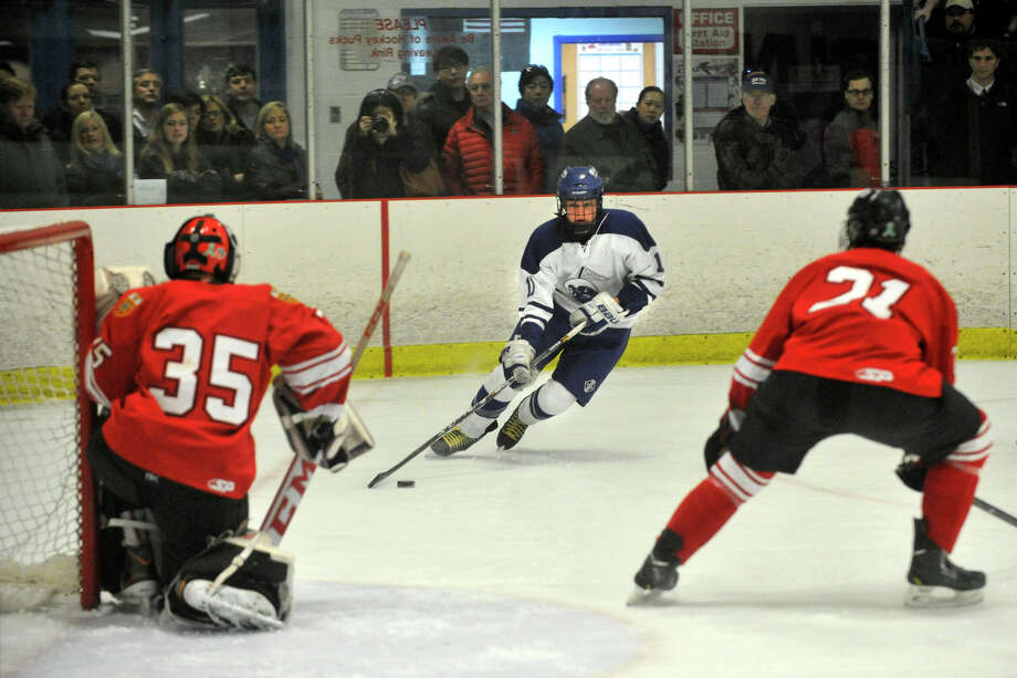 Darien's Nicholas Tuzinkiewicz eyes the Fairfield Prep goal that is guarded by goalie Christopher Gutierrez, left, and Bryan Connell during their hockey game at Darien Ice Rink in Darien, Conn., on Feb. 6, 2014. Darien won in overtime, 3-2. Photo: Jason Rearick / Stamford Advocate