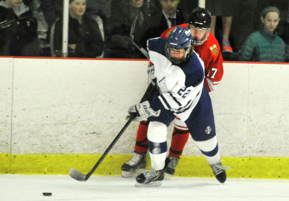 Darien's Jack Pardue passes the puck with Fairfield Prep's Ryan Deering providing pressure from behind during their hockey game at Darien Ice Rink in Darien, Conn., on Feb. 6, 2014. Darien won in overtime, 3-2. Photo: Jason Rearick / Stamford Advocate