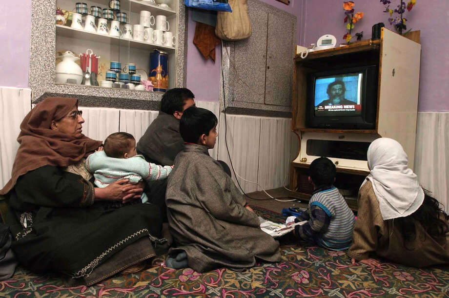 A Kashmiri Muslim family watches television in downtown area of Srinagar, India, in 2003. A study has drawn a parallel between obesity and diabetes and ownership of televisions, computers and cars in low-income countries. Photo: Associated Press / AP