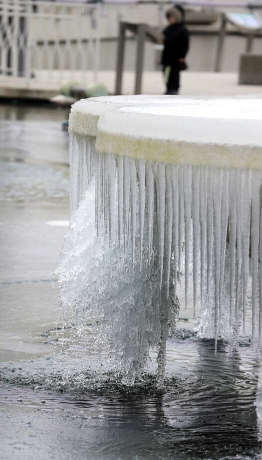 Ice builds up on a fountain at the Pacific Science Center in Seattle, Thursday, Feb. 6, 2014. Below-normal, frigid temperatures are forecast to continue into the weekend. Things will start warming up into the 40s by Sunday. (AP Photo/Ted S. Warren) Photo: Ted S. Warren, AP