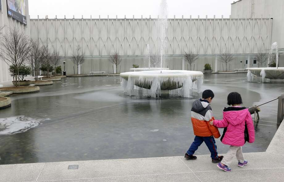 Two kids on a school outing walk past a frozen fountain at the Pacific Science Center on Feb. 6, 2014. (AP Photo/Ted S. Warren) Photo: Ted S. Warren, AP