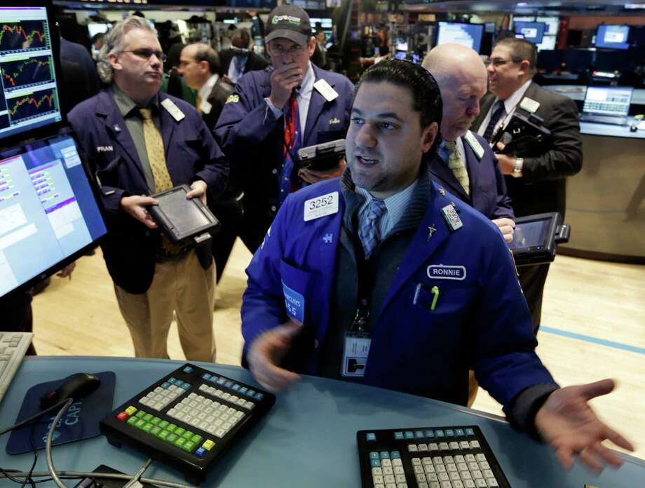 FILE- In this Wednesday, Feb. 5, 2014, file photo, Specialist Ronnie Howard, foreground, works at the post that trades CVS Carremark, on the floor of the New York Stock Exchange. Australia's stock market and currency jumped Thursday Feb. 6, 2014 after encouraging economic data while gains on other major world benchmarks were more modest as investors waited for key policy meetings in Europe and a major U.S. job report.  (AP Photo/Richard Drew, File) Photo: Richard Drew, STF / AP