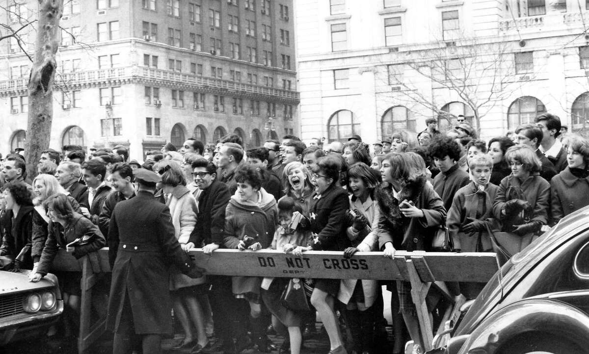 Police enforce the barricades outside New York's Plaza Hotel as fans push forward in hopes of a view of The Beatles after their arrival for an American tour on February 7, 1964.