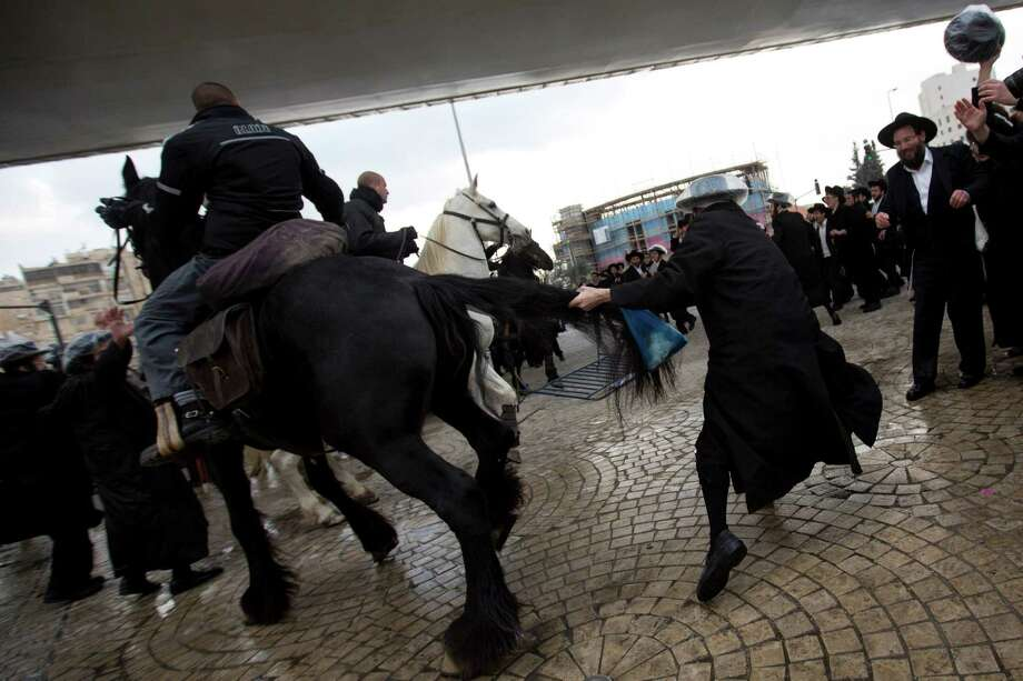 Israeli police officers on horses disperse a crowd of ultra-Orthodox Jewish men during a demonstration in Jerusalem on Thursday. Thousands of ultra-Orthodox Jews blocked highways across the country. Photo: Sebastian Scheiner, STF / AP