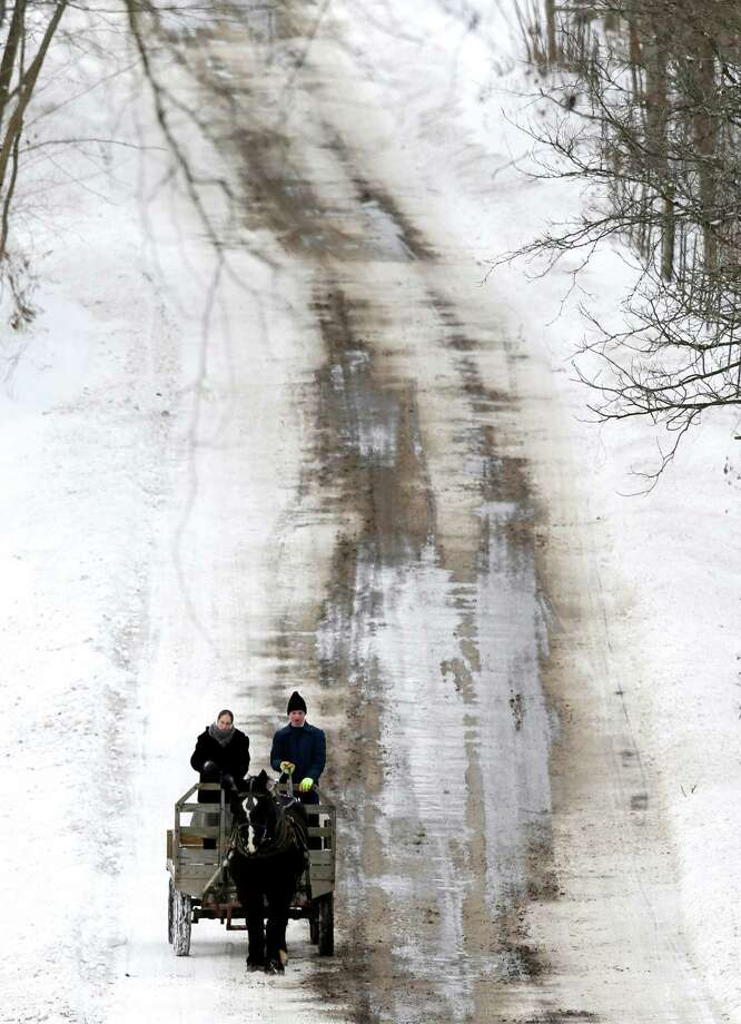 Snow tires or chains aren't needed on this Amish buggy as it carries two passengers slowly down a steep hill Thursday near Middlefield, Ohio. Photo: Tony Dejak, STF / AP