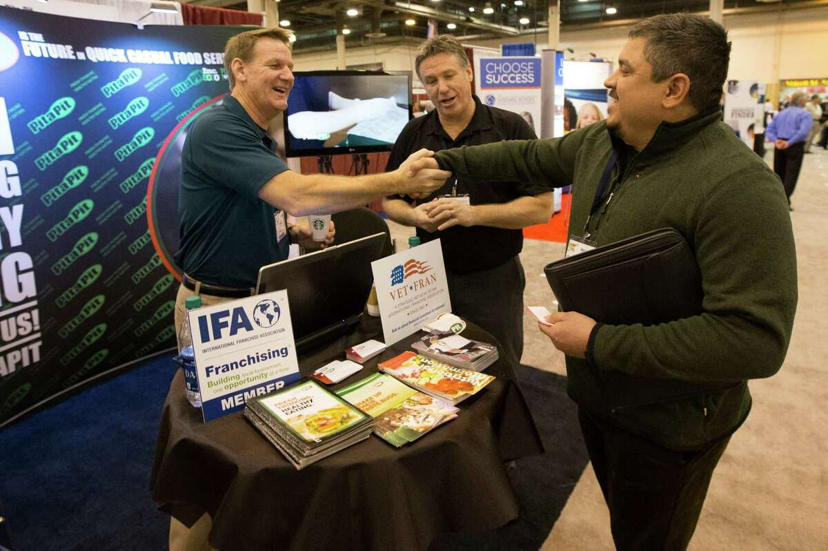 Entrepreneur Chris Fonseca, right, talks with Dirk Ferrell, left, and Bill Wilfong of Pita Pit as he walks through the Franchise Expo in Reliant Center on Thursday, Feb. 6, 2014, in Houston. Fonseca, 42, is looking to buy a franchise. ( J. Patric Schneider / For the Chronicle )