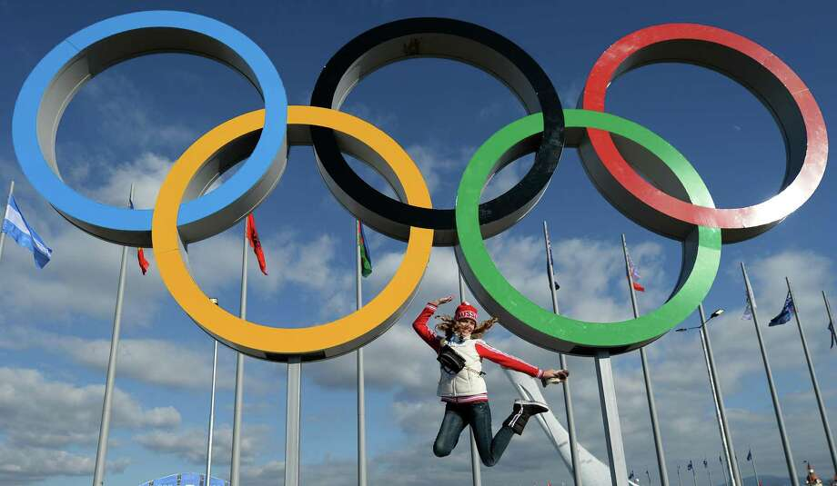The threat of terrorism and anxiety surrounding the 2014 Winter Games in Sochi, Russia, seem lost on this young woman, who cavorts for a photograph under the Olympic rings Thursday. Photo: ANDREJ ISAKOVIC, Staff / AFP