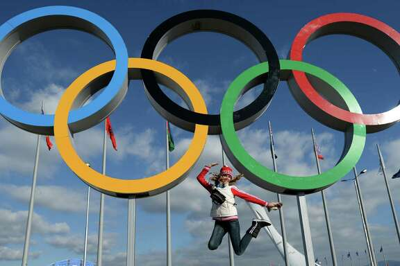The threat of terrorism and anxiety surrounding the 2014 Winter Games in Sochi, Russia, seem lost on this young woman, who cavorts for a photograph under the Olympic rings Thursday.