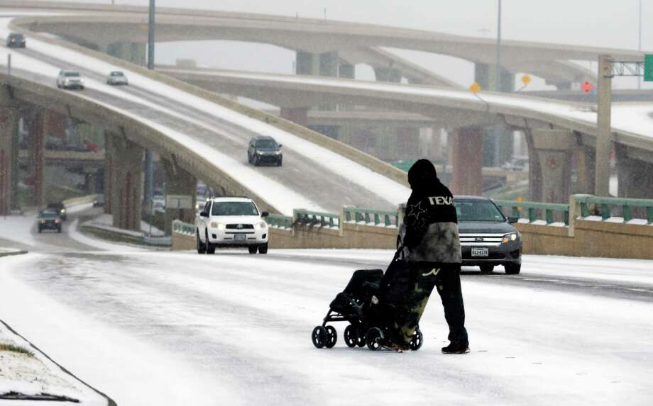 A man pushes an empty stroller on a snow covered street in Dallas, Thursday, Feb. 6, 2014. A light snow made the morning commute difficult for a metropolitan area not accustomed to winter precipitation. (AP Photo/LM Otero) Photo: LM Otero, STF / AP