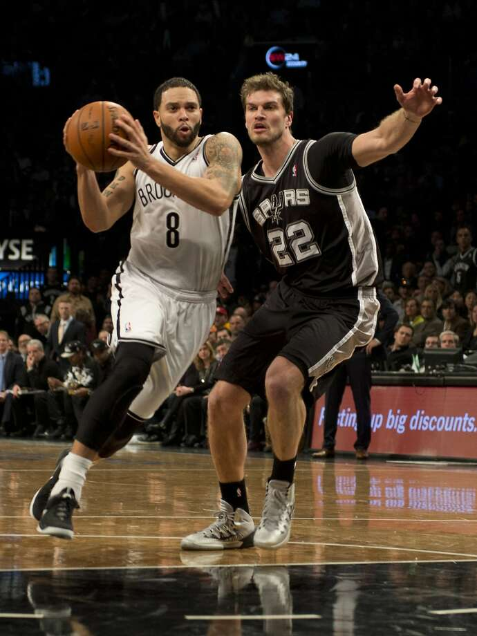 Deron Williams drives by the Spurs' Tiago Splitter. The Nets' guard had 16 points. Photo: Don Emmert, AFP/Getty Images