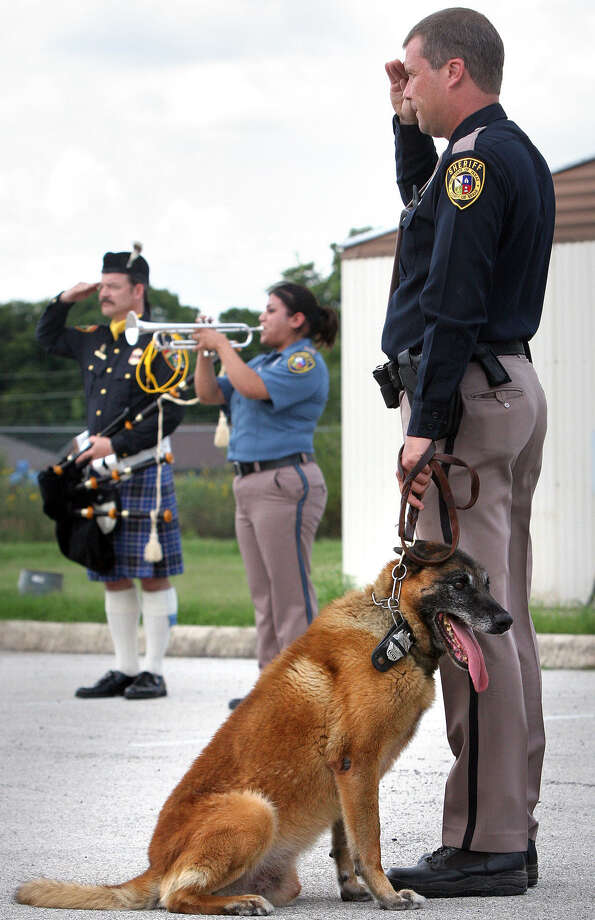 Deputy Steve Benoy (right) of the Bexar County Sheriff K9 Unit  is shown at a police dog's 2007 memorial service. He now has been indicted for the heat exhaustion deaths of two police dogs after allegedly leaving them in a hot patrol vehicle overnight. Photo: Bob Owen / San Antonio Express-News / SAN ANTONIO EXPRESS-NEWS