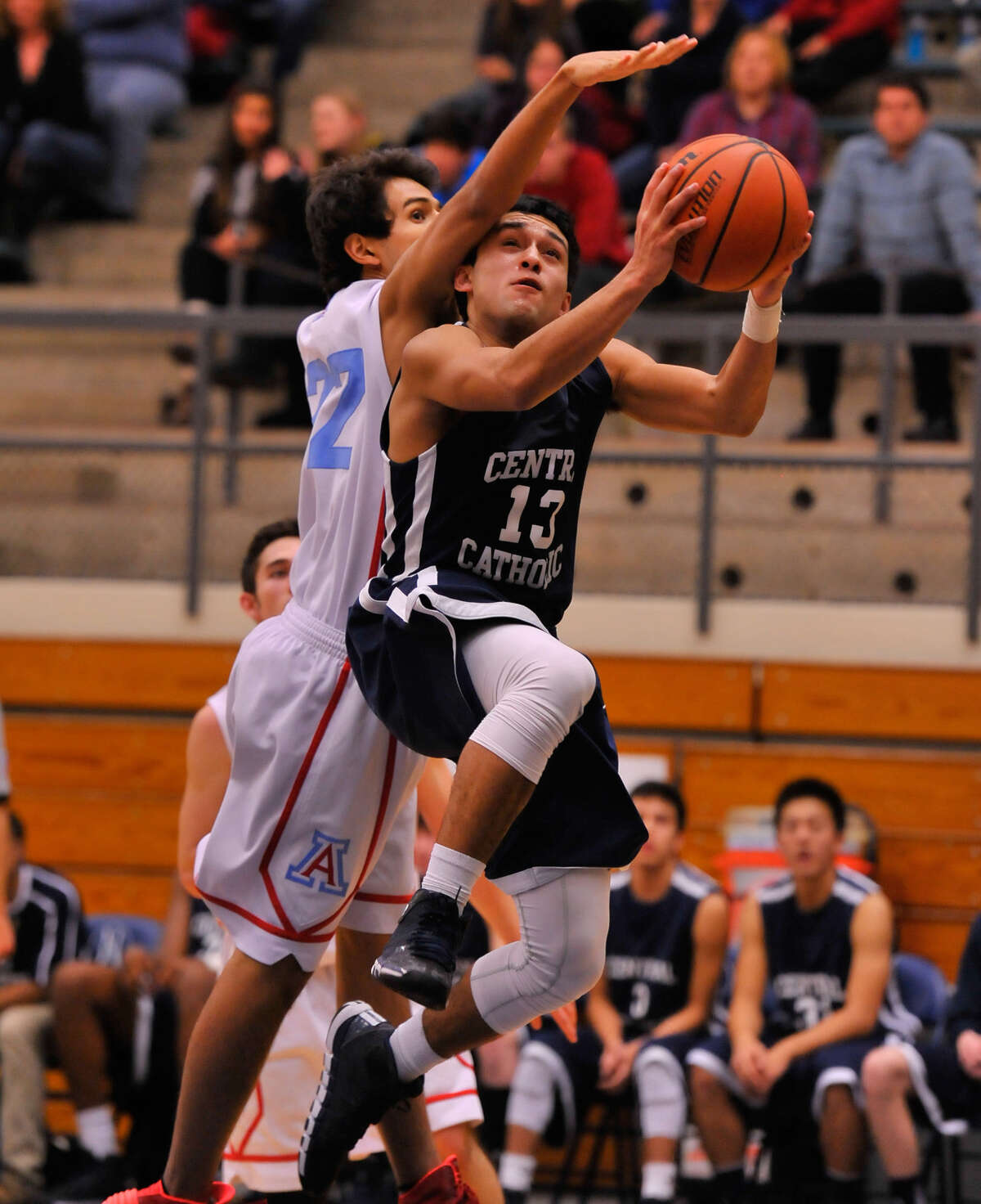 Central Catholic's P.J. Escobar (25 points) tries to score around Antonian's Christian Rodriguez at Taylor Field House during a game Feb. 6, 2014. The Buttons won 66-55.
