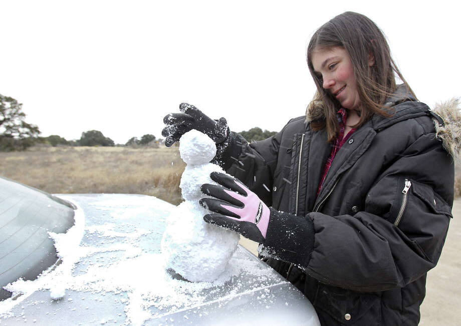 Miniature snowmen were a hot commodity on Thursday, as Hailey Baur demonstrates by constructing one on the back of a car in her yard north of New Braunfels. Photo: Tom Reel / San Antonio Express-News