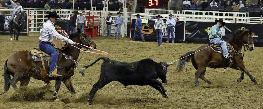 Clay O'Brien Cooper of Gardnerville, Nev., (left) and Chad Masters of Cedar Hill, Tenn., compete in the team roping event during Thursday's action at the San Antonio Stock Show & Rodeo. The team's time was 6.0 seconds. Photo: Photos By Edward A. Ornelas / San Antonio Express-News / © 2014 San Antonio Express-News