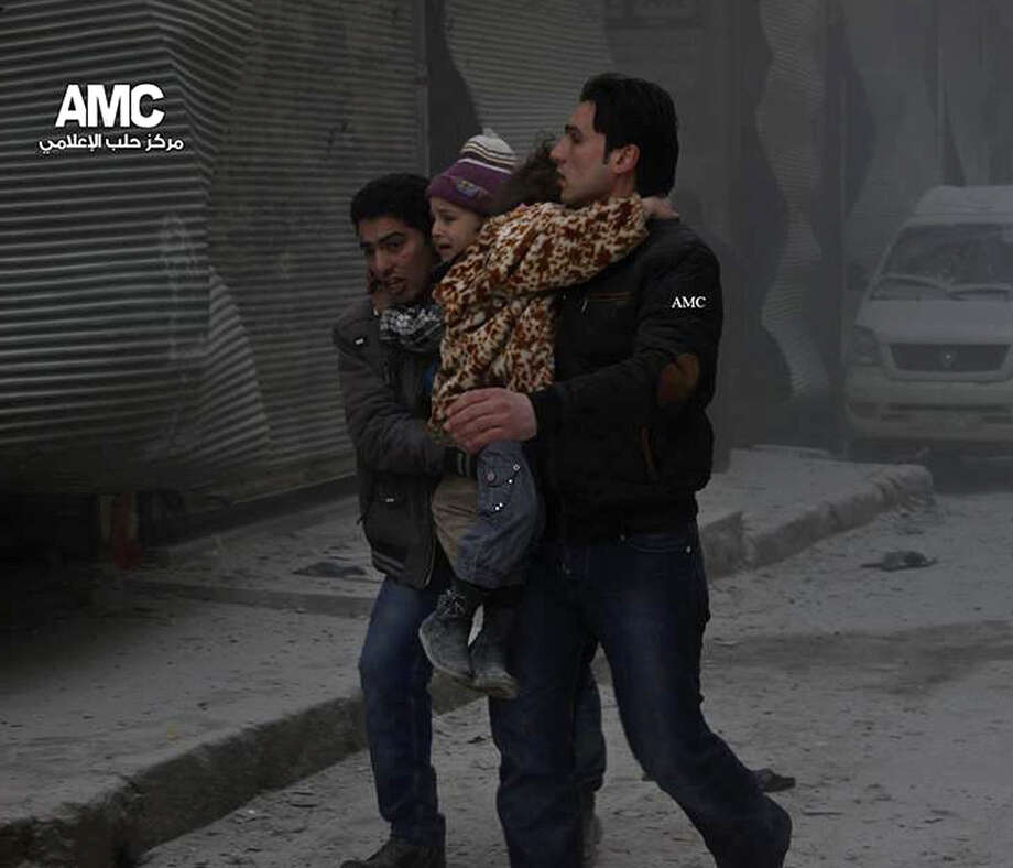 Men carry young survivors out of a building that was destroyed in an attack by Syrian warplanes in Aleppo that activists said killed dozens of people, 17 of them children, on Sunday. Photo: Aleppo Media Center / Associated Press / Aleppo Media Center AMC