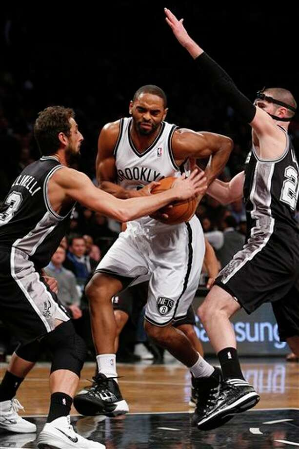 Brooklyn Nets' Alan Anderson, center, is fouled as he drives between San Antonio Spurs' Marco Belinelli (3), of Italy, and Nando De Colo, right, of France, during the second half of an NBA basketball game on Thursday, Feb. 6, 2014, in New York.  Brooklyn won 103-89. (AP Photo/Jason DeCrow) Photo: Jason DeCrow, AP / FR103966 AP