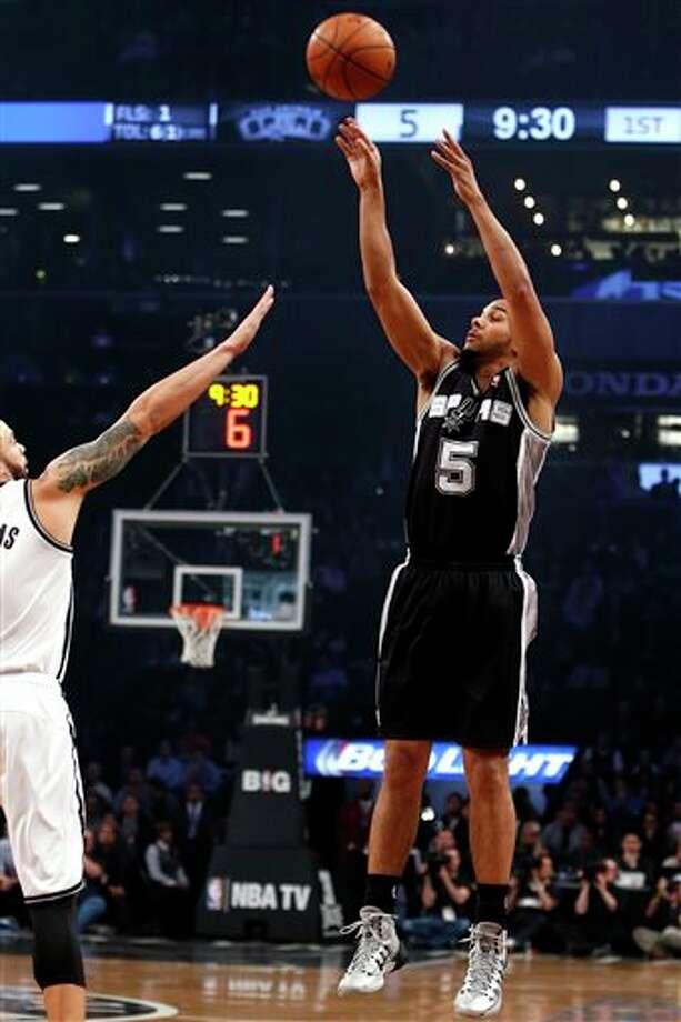 San Antonio Spurs' Cory Joseph (5) shoots against Brooklyn Nets' Deron Williams during the first half of an NBA basketball game on Thursday, Feb. 6, 2014, in New York. (AP Photo/Jason DeCrow) Photo: Jason DeCrow, AP / FR103966 AP